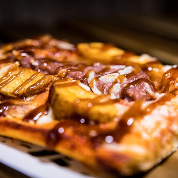 Pizzone, Porciones de Pizza PIZZburguer con Tomate italiano especiado, hambureguesa mixta, patatas de luxe, salsa BBQ y queso mozzarella.