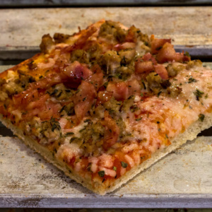 Pizzone, Porciones de Pizza de Bacon y Pollo con Tomate italiano especiado, bacon al horno, pechuga de pollo asada, orégano, queso mozzarella.