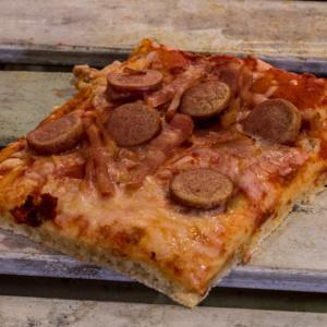 Pizzone, Porciones de Pizza de Bacon y Salchichas. Tomate italiano especiado, bacon al horno, salchichas frankfurt, queso mozzarella.