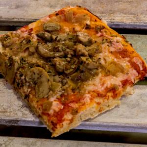Pizzone, Porciones de Pizza de Cebolla y Champiñón. Tomate italiano especiad, bacon al horno, cebolla, champiñón, orégano y queso mozzarella.