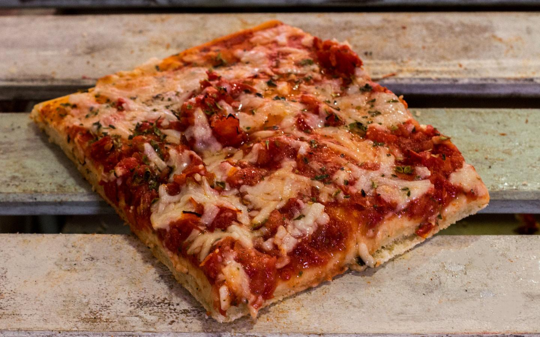 Pizzone, Porciones de Pizza Margarita. Tomate italiano especiado, rodajas de tomate, ajo, perejil, orégano, aceite de oliva y queso mozzarella.