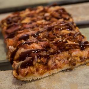 Pizzone, Porciones de Pizza de Bacon BBQ. Tomate italiano especiado, bacon al horno con salsa BBQ y queso mozzarella.